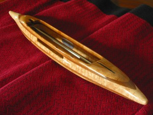 "B6Shuttle6: Curly cherry top/bottom, black walnut 2nd layers, bird's eye maple center. 4.8oz., 14 3/8""L, 1 3/4""W, 1 1/16""H, 3 3/4"" cavity end to tip. Fits 6"" bobbins."