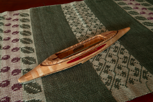 s2018exbashbemapl4: Ash burl top/bottom, black walnut 2nd layers, bird's eye maple center.  Pink ivory yarn slot inlay. 3.8 oz., 12 1/2″L, 1 3/4″W, 1 1/16″H, 3 5/8″ tip to nearest cavity end. Fits 4″ bobbins.